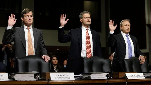 Drei Männer stehen mit erhobener rechter Hand hinter ihren Stühlen.