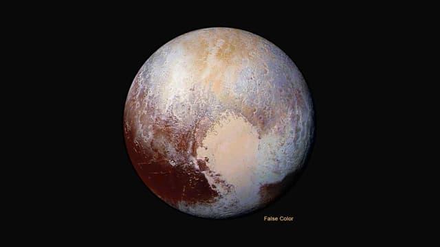 Pluto als Kugel. In der unteren Hälfte hebt sich eine weissliche, herzförmige Fläche vom Rest des Planeten ab.