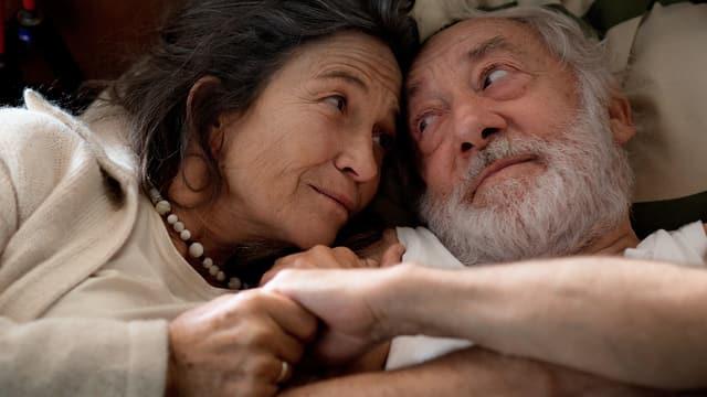 Ein älteres Paar liegt sich in den Armen.