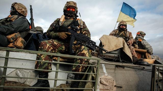 Ukrainische Soldaten sitzen bewaffnet auf einem Panzerfahrzeug.