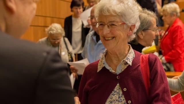 Mehrere Seniorinnen mit Büchern und Papier in der Hand in einer Halle.