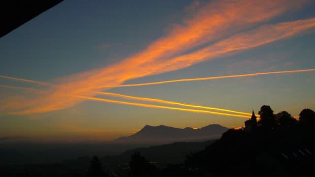 Zahlreiche orange Kondensstreifen am Himmel über Kriens.