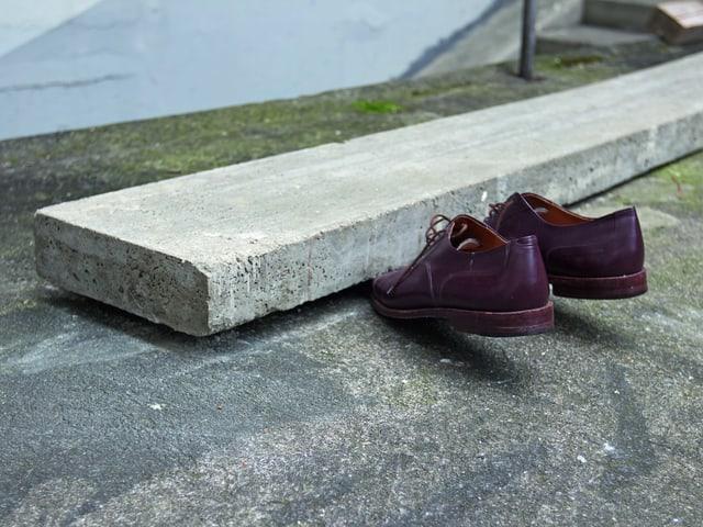 Zwei Schuhe unter einem Betonstreifen