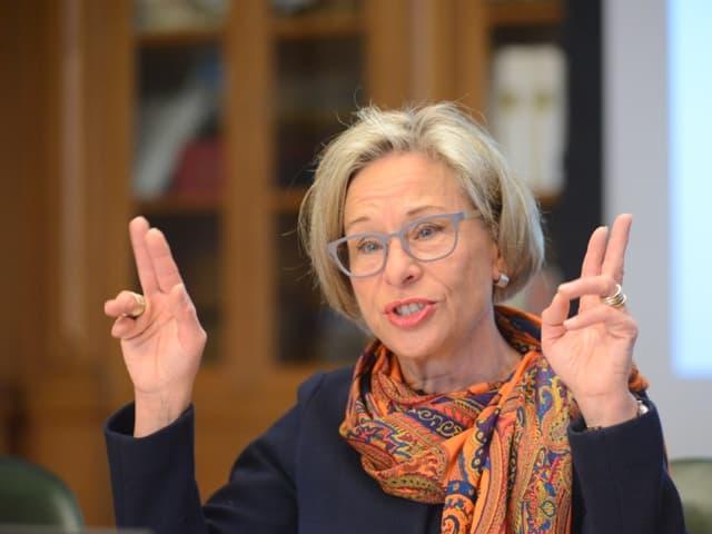 Eine Frau mit grauen Haaren und hellblauer Brille zeichnet mit den Händen Anführungszeichen in die Luft.