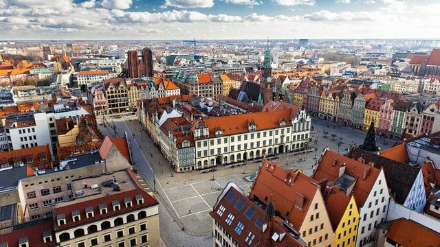 Ausblick über eine Grosstadt mit vielen Ziegeldächern und wenig Hochhäusern.
