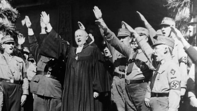 Ein Bischof inmitten von uniformierten Nazis. Alle machen den Hitlergruss