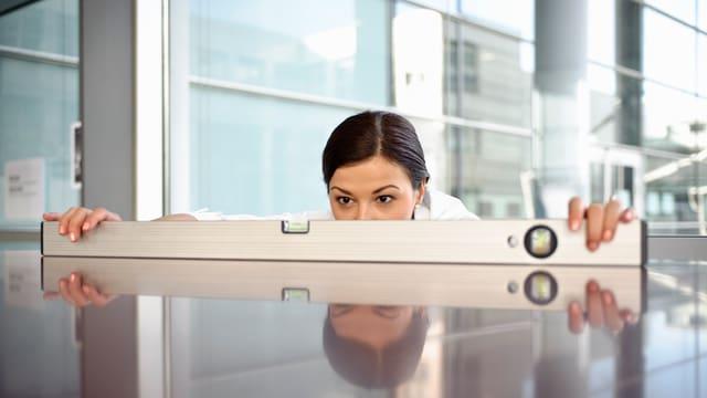 Eine Wasserwaage auf einem spiegelenden Tisch, dahinter zur Hälfte sichtbar das Gesicht einer dunkelhaarigen Frau.