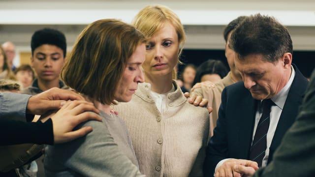 Ruth (Judith Hofmann) wird im Kreis einer Freikirche von diversen Händen berührt.