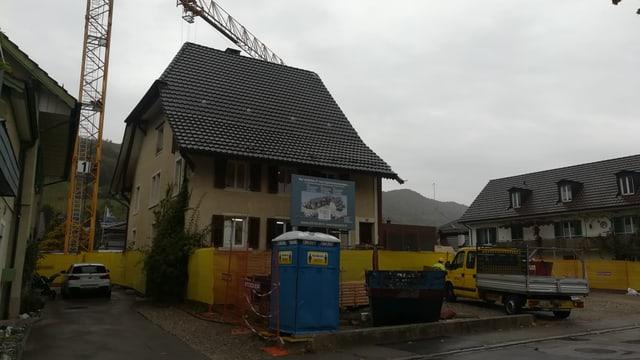 Haus mit Kran und Bauabschrankungen.