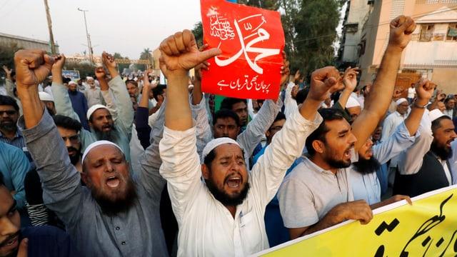 Protestierende Männer mit Bart schreiben Parolen, einer hält ein rotes Transparent mit pakistanischen Schriftzeichen in die Höhe.