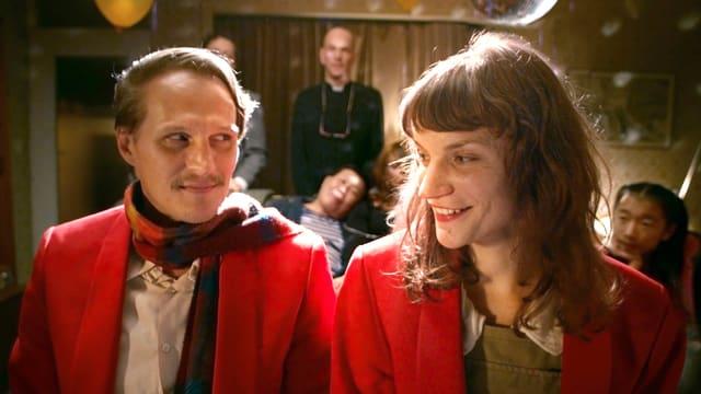 Ein Mann und eine Frau, beide in Mänteln. Er guckt sie verschmitzt an, sie lächelt.