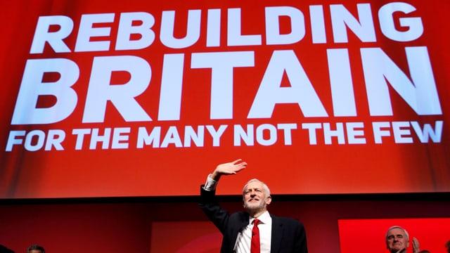 """Labour-Chef Corbyn klein unter einem roten Banner mit der weissen Aufschrift """"Rebuilding Britain for the many not the fews""""."""