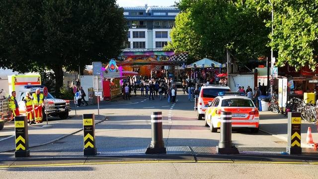 im Hintergrund ein Strassenfest, im Vordergrund Polizeiautos und schwarz/gelbe Poller