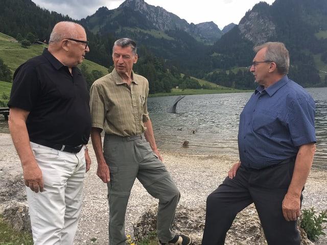 Drei Männer stehen auf einem Kiesstrand.