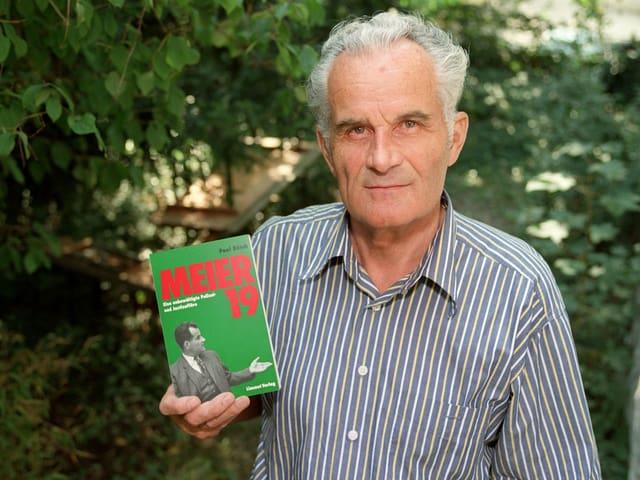 Kurt Meier mit einem Buch in der Hand, das seine Geschichte beschreibt.