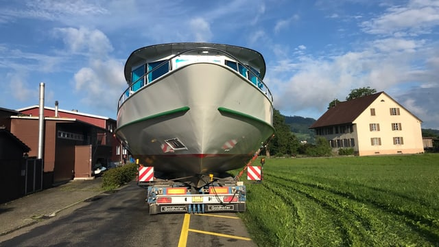 Das grosse Schiff wird angeliefert auf einem Lastwagen. Er fahrt auf einer kleinen, schmalen Strasse.