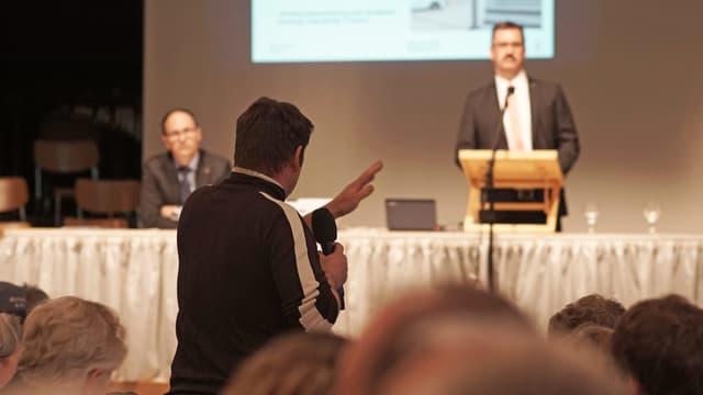 Köpfe im Vordergrund, eine Person mit Mikrophon und zwei Personen auf Bühne