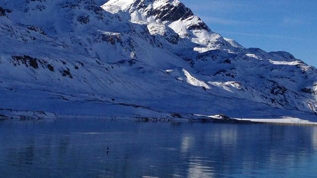 Das schwarze Eis auf dem Lago Bianco spiegelt den Berg in seiner ganzen Pracht.