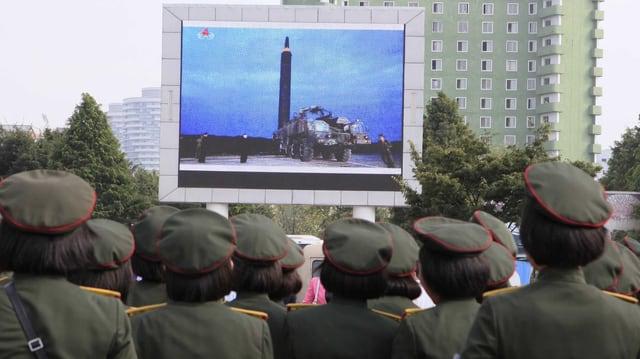 Uniformierte schauen auf einen grossen Bildschirm, der eine Rakete zeigt.