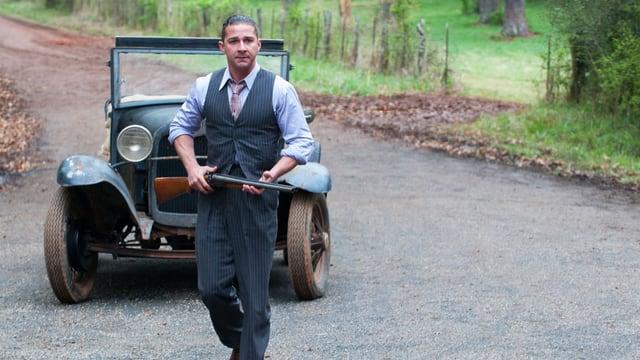 Der Schauspieler Shia LaBeouf mitten auf der Strasse vor einem Auto, das Gewehr im Anschlag