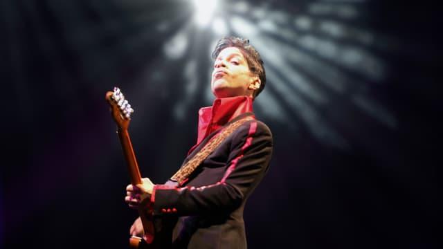 Prince spielt Gitarre, hinter seinem Kopf leuchtet ein Scheinwerfer.