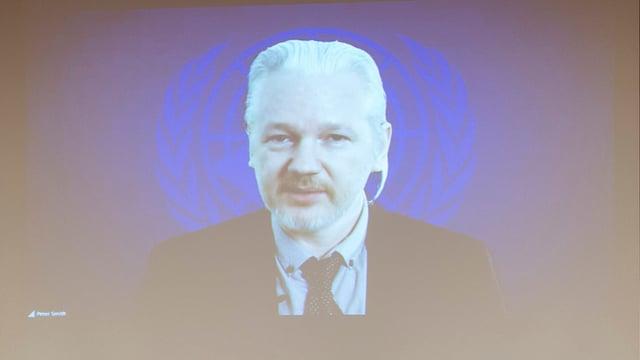 Julian Assange auf einer Leinwand mit UNO-Wappen im Hintergrund