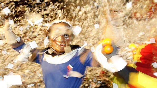 Ein maskierter Fasnachts-Besucher im Fötzeliregen.