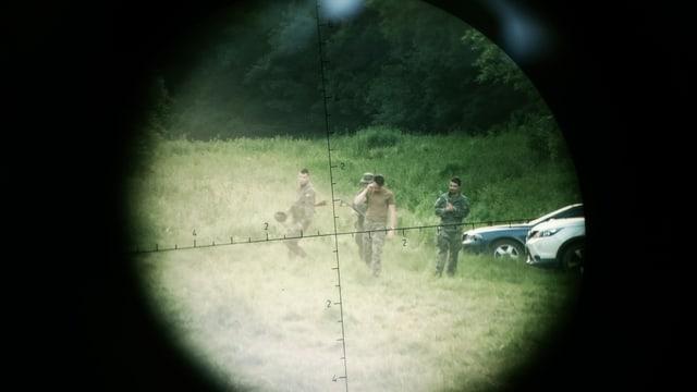 Zielfernohr auf Soldaten auf Wiese gerichtet.