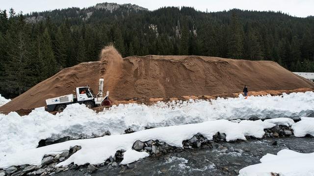 Ein Berg an Schnee wird in Davos mit Sägemehl zugedeckt.