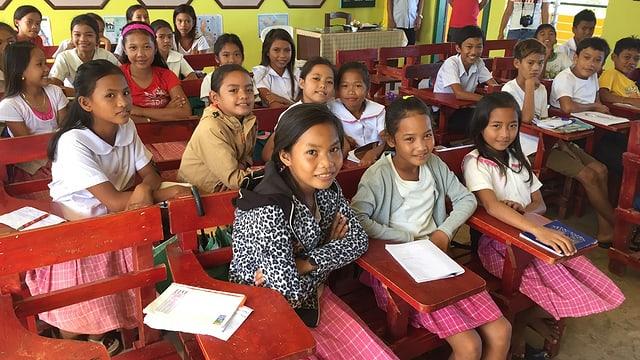 Schüler in einem Zimmer an ihren Tischen.