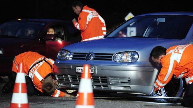 Zürcher Kantonspolizisten untersuchen ein Auto.