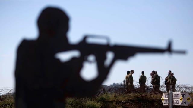 Umrisse eines Mannes mit Maschinengewehr im Anschlag, im Hintergrund eine Gruppe Soldaten.