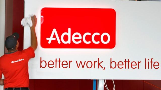 Angestellter einer Reinigungsfirma putzt das Adecco-Logo an einem Firmengebäude