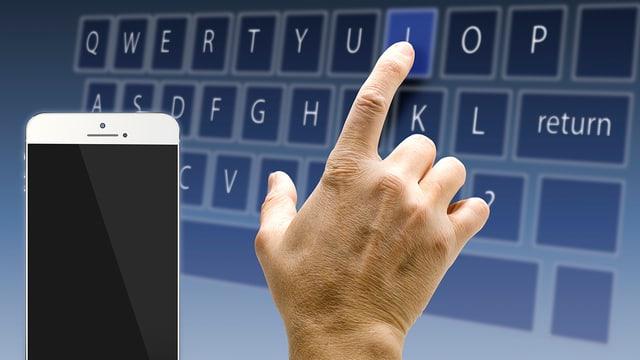 Symbol-Bild: Hand vor einem Bildschirm mit Software Tastatur.