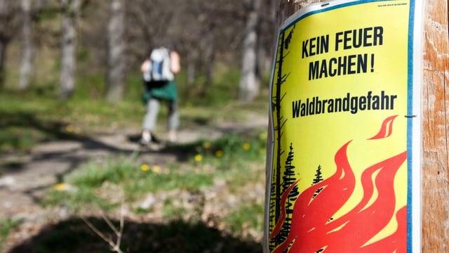 Ein Schild warnt Wanderer in einem Wald vor grosser Waldbrandgefahr.