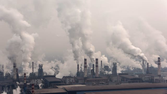 Luftaufnahme: Fabrikgelände mit etlichen, rauchenden Schloten.