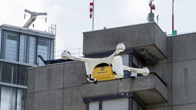 Eine Drohne mit Postpaket vor dem Inselspital.