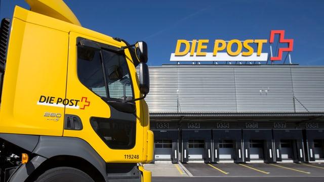 Gelber Lastwagen der Post mit Logo vor dem Paketzentrum Härkingen, auf dessen Dach ebenfalls ein Post-Logo angebracht ist