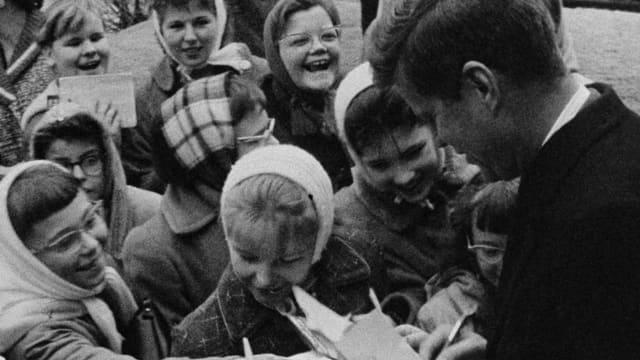 John F. Kennedy gibt Autogramme.