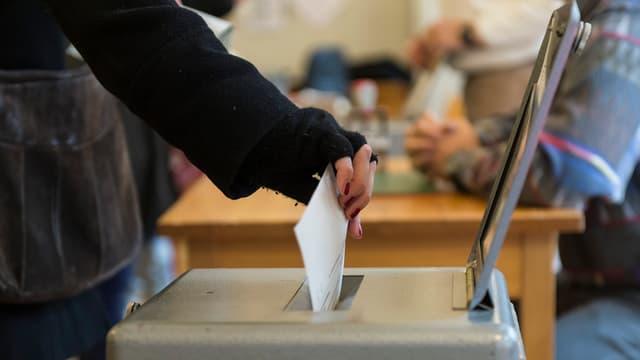Frau wirft Stimmzettel in die Urne