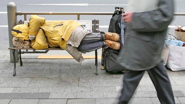 Ein Geschäftsmann geht an einem obdachlosen Mann vorbei, der auf einer Bank schläft. (reuters)