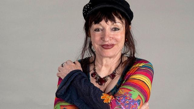Porträt der Schauspielerin Yvette Théraulaz, die eine schwarze Mütze und einen bunten Pullover trägt und in die Kamera lächelt.