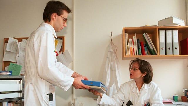 Ein Assistenzarzt überreicht einer Kollegin Krankenakten