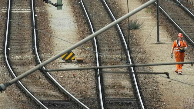 Ein Arbeiter geht in München über die Gleise.