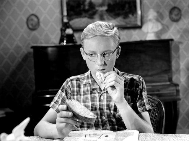 Ein blonder Jugendlicher sitzt an einem Tisch und hält ein belegtes Brot in der einen Hand. Die andere Hand führt er sich gerade mit einem weiteren Bissen zum Mund.