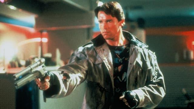 Ein Mann in einem Ledermaten hält eine futuristische Pistole in den Händen.