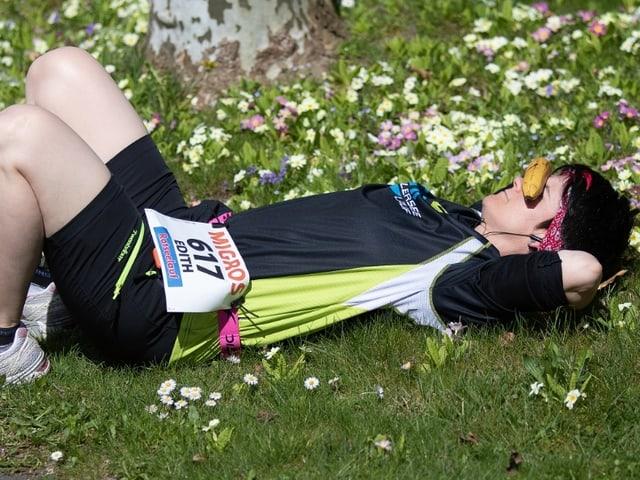 Eine Frau liegt in einer Blumenwiese.