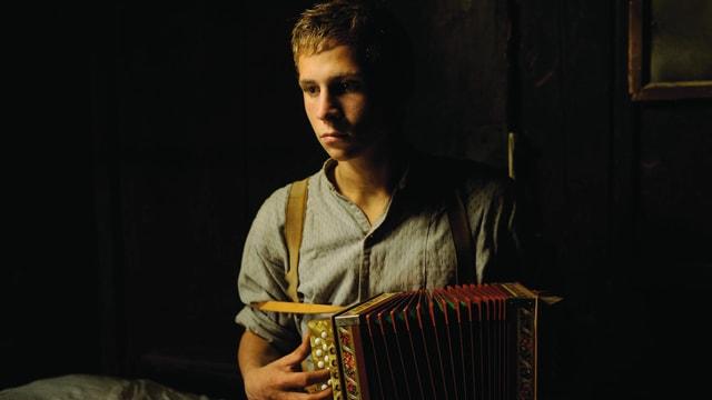 Ein junger Mann spielt mit einer Handorgel.