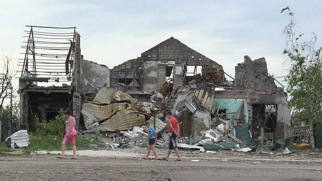 Drei Leute laufen vor einem ausgebombten Haus vorbei.