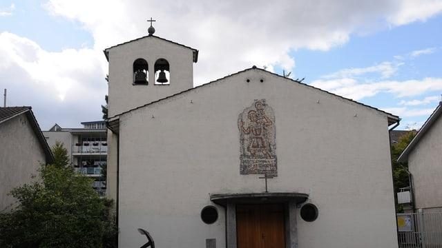 Frontalansicht der Kirche - einfache Fassade mit Porte, Glockenturm niedrig links
